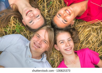 Four young happy people lying on the ground