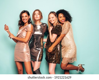 Four young international beautiful brunette women in trendy summer  shiny dress.Sexy smiling carefree female posing near blue wall in studio.Fashionable models with bright evening makeup - Shutterstock ID 1921221629