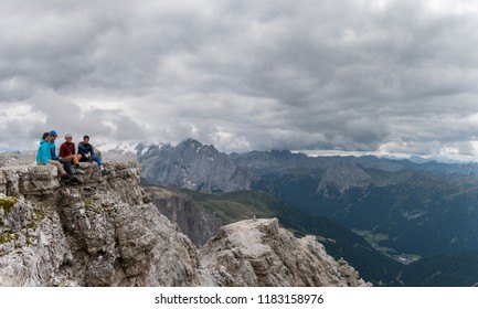 four young male and female hikers sitting on a mountain peak ledge in the Dolomites and looking at the amazing view with Langkofel and Marmolada peaks