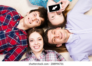 four young men lie together, young attractive woman pressed her lips to the phone