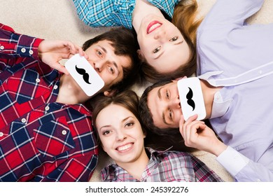 four young men lie together, applied to the face plate with a mustache