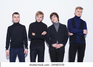 Four young men  standing in full length near the wall, looking in different directions, over white background