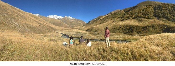 Four young millennials taking a rest after a long hike in Juta, Georgia with picturesque mountain and river backdrop