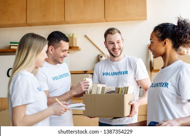 four young multicultural volunteers talking while holding cardboard box with books