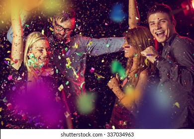 Four young people having fun and dancing at a party