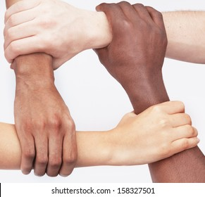 Four young people holding each others wrists in a circle