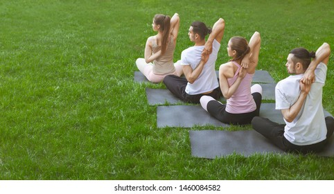 Four young people practicing yoga outdoors, sitting in Vajrasana pose with hands hooked behind the back. Back view, panorama with copy space