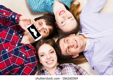 four young people are together, the young man pressed his lips to the phone