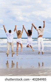 Four young people, two couples, holding hands, having fun and jumping in celebration on a beach