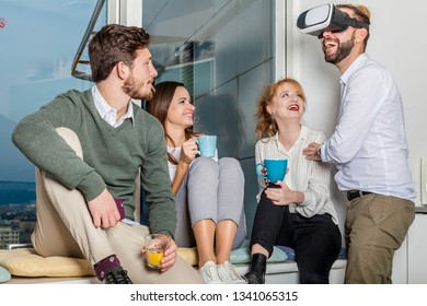 four young professionals have a break and making fun jokes with vr goggles. they drink coffee and tea and lead one colleage. casual friday after work concept.