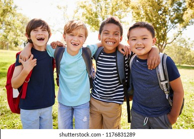 Four young smiling schoolboys hanging out on a school trip