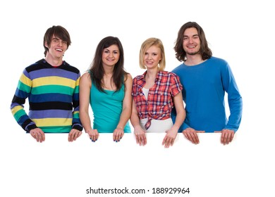 Four young students standing behind white blank banner and smiling. Waist up studio shot isolated on white.