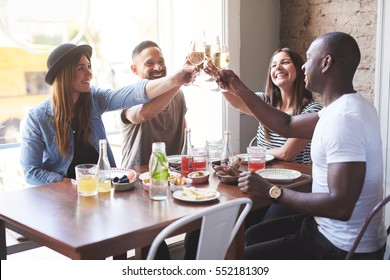 Four young stylish smiling people sitting at table having dinner and clinking glasses with wine.