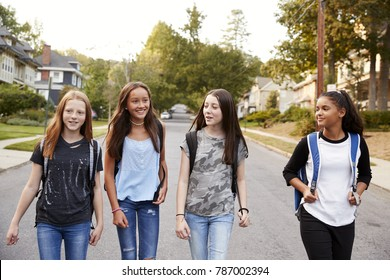 Four young teen girls walking in the road, close up