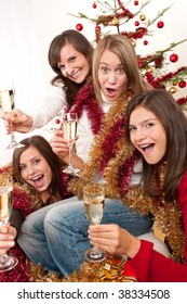 Four young woman having fun on Christmas with champagne