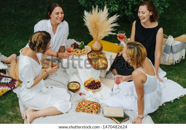 Four young women are drinking wine and making conversation during picnic, sitting on white tablecloth next to variety of appetizers. Three are dressed in white and one in black.