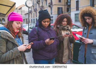 four young women multiethnic outdoor using smart phone outdoor - phubbing, social network, communication concept