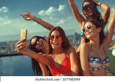 Four young women in a penthouse near the pool doing selfie in a bikini