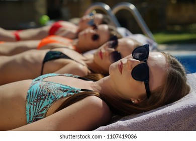 Four young women sunbathing in bikinis on the sun chairs by swimming pool