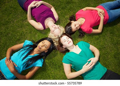 Four young women sunbathing in a park with eyes closed