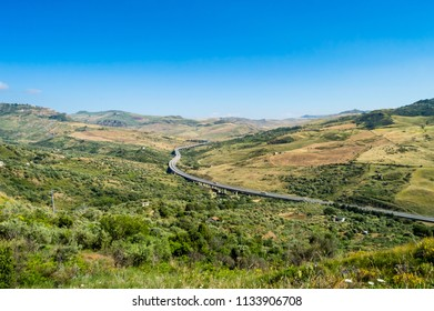 Four-lane highway spiraling through the countryside and hills of northwestern Sicily