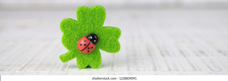 Four-leaf clover with ladybug on wooden background, banner