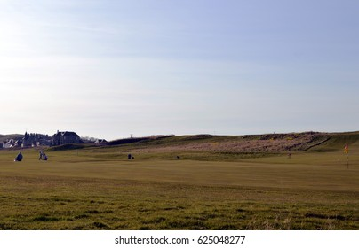 A foursome play in early spring evening light to the 18th hole on the Earlsferry links course at Elie Golf Club House, Fife, Scotland