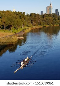 foursome rowing in the foreground and cityscape in the background
