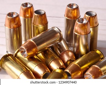 Fourteen different 40 caliber hollow point bullets together on a white wooden background. The bullets have silver cases on several and brass on the others
