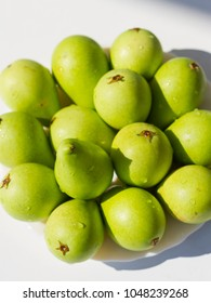 Fourteen fresh, green, pears, delicious fruit, on a white plate in the sunlight;
