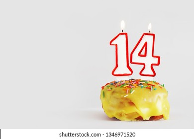 Fourteen  years anniversary. Birthday cupcake with white burning candles with red border in the form of number Fourteen. Light gray background with copy space