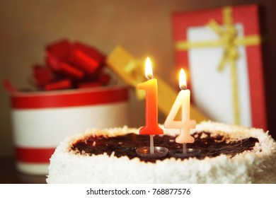 Fourteen years birthday. Cake with burning candle and gifts