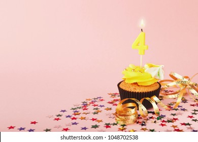 Fourth birthday cupcake with candle and sprinkles on pink background. Card mockup, copy space. Birthday, party, holiday concept
