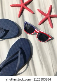 Fourth of July / American Summer concept. Flip flops and sunglasses.