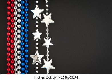 Fourth of July Background with Red, White, and Blue beads with Silver Stars on Blank Black Background with room or space for copy, text, your words.  Horizontal flat layout that works as vertical