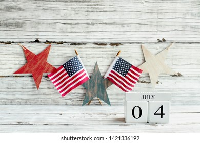 Fourth of July Background. Wood calendar blocks with the date July 4th to mark America's Independence Day. American flags with a star shaped banner hanging.