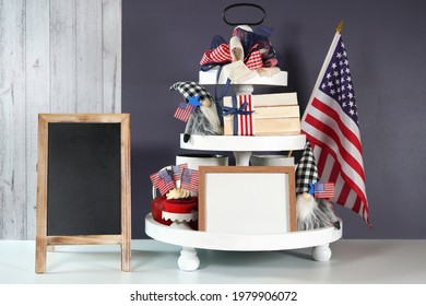 Fourth of July Independence Day theme. On-trend farmhouse aesthetic three tiered tray decor filled with gifts, cute black plaid gnomes, and farmhouse style stack of books mockup. Negative copy space. - Shutterstock ID 1979906072