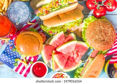 Fourth of July, Memorial Day, USA Independence Day concept. Patriotic, American traditional food. Picnic party with watermelon, burgers, hot dogs, drinks, blue wooden outdoor table background