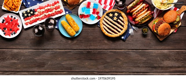 Fourth of July, patriotic, American themed food. Overhead view top border on a dark wood banner background. Copy space.