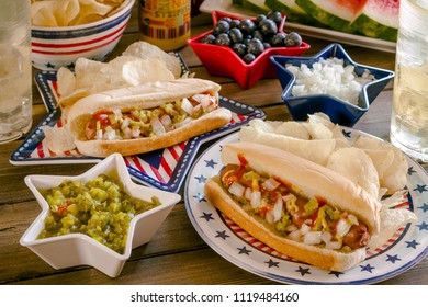 Fourth of July picnic table with hot dogs, chips, watermelon and lemonade