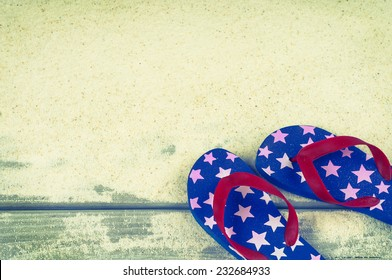 Fourth of July Rubber Sandal Flip-Flop Thongs on Wood Boardwalk and White Sand background with room or space for copy, text, your words.  Vintage instagram, horizontal warm tone