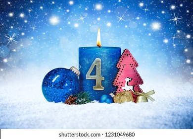 fourth sunday of advent blue candle with golden metal number red decoration one on wooden planks in snow front of silver panorama bokeh background