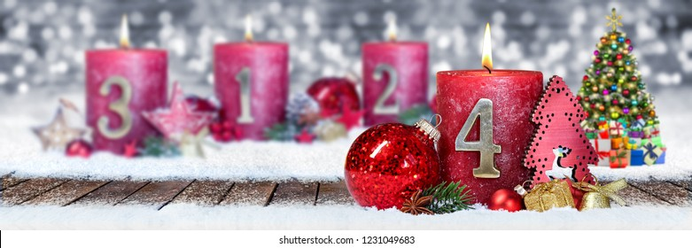 fourth sunday of advent red candle with golden metal number one on wooden planks in snow front of silver panorama bokeh background