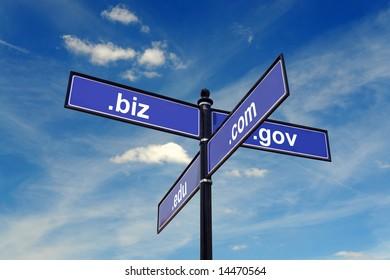 Four-way metal signpost spelling COM, BIZ, EDU, GOV domains over blue sky