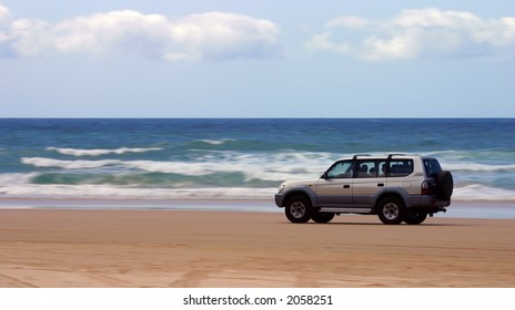 Four-wheel-drive SUV moving on a beach with motion blur on the background (Fraser Island, Australia)