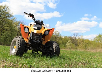 A four-wheeled yellow ATV quad-bike standing idle on the green grass, with trees and a blue sky with clouds on the background.