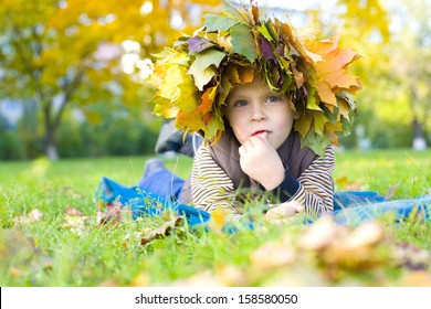 Four-year boy lying on the grass in a wreath of autumn leaves