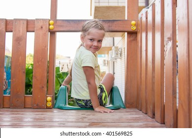 Four-year girl sitting on a wooden platform personal game complex