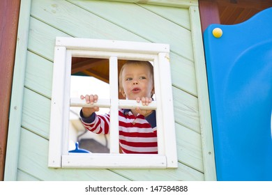 four-year-old boy who is looking out in a window of a children's lodge