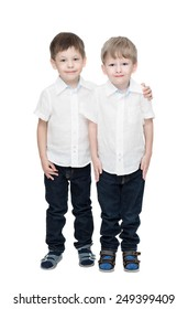 Four-year-old boys of twins, in white linen shirts, one embraces another, isolated on the white